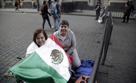 Con una bandera estas mujeres quieren hacerse ver al paso del Papa, en este retén de los muchos que mantienen a buena parte de la capital mexicana con el alma en un hilo a la espera del viajero