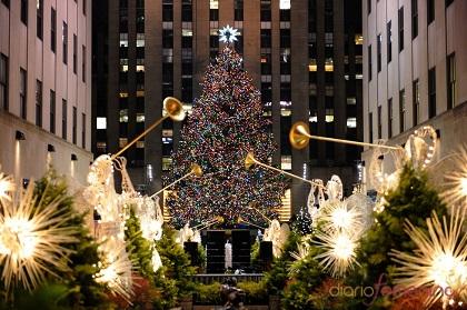 Luces de Nueva York, en el Rockefeller Center, querubines y arcángeles dorados y sus trompetas celestiales custodian al pino que corona la Estrella de Belén. La Manzana o Urbe de Hierr cuenta las horas para la cita anual.