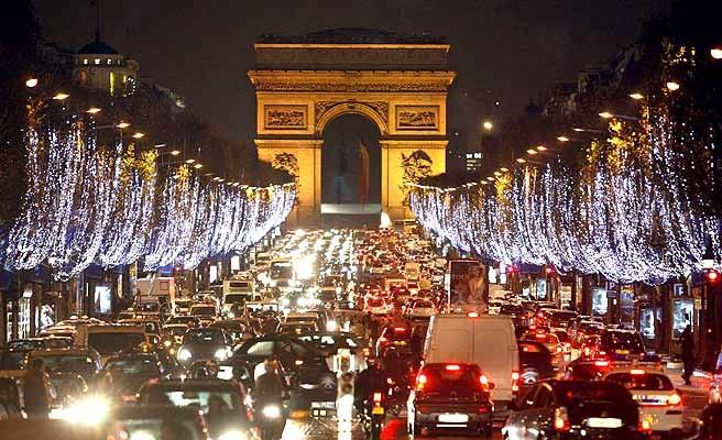 Así está Paris, que nunca duerme ¡oh Paris! Cascadas plateadas luminosas frente al Arco del Triunfo dominan Les Champs Elysees y miles de parisinos en la euforia de las compras previas a la cita anual.